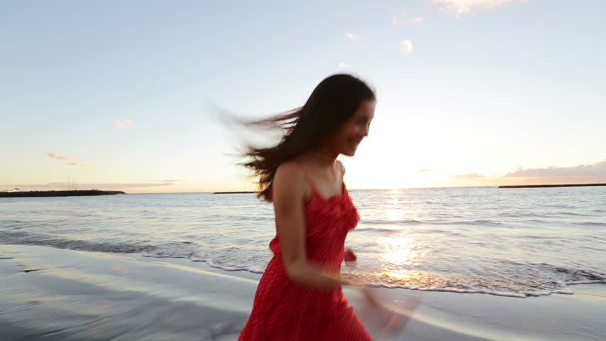 Happy woman running on beach in summer dress cheerful, energetic and vivacious full of joy. Casual girl having fun during vacation travel. Beautiful mixed race Asian Caucasian female model in her 20s