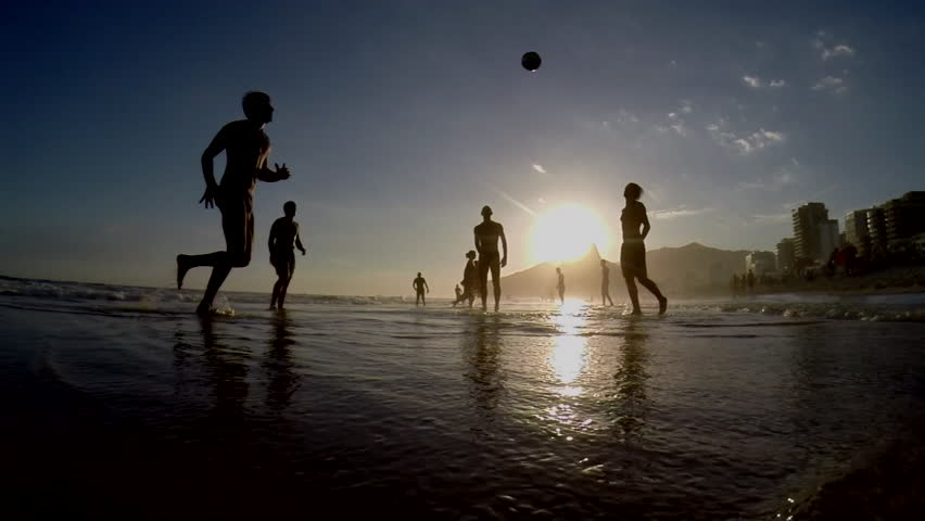 Silhouettes of Carioca Brazilians playing beach football at sunset on Ipanema Beach Rio de Janeiro Brazil silhouetted slow motion