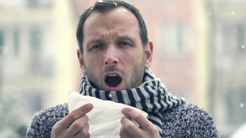 Sick man blowing nose in snowy weather, super slow motion, shot at 240fps
