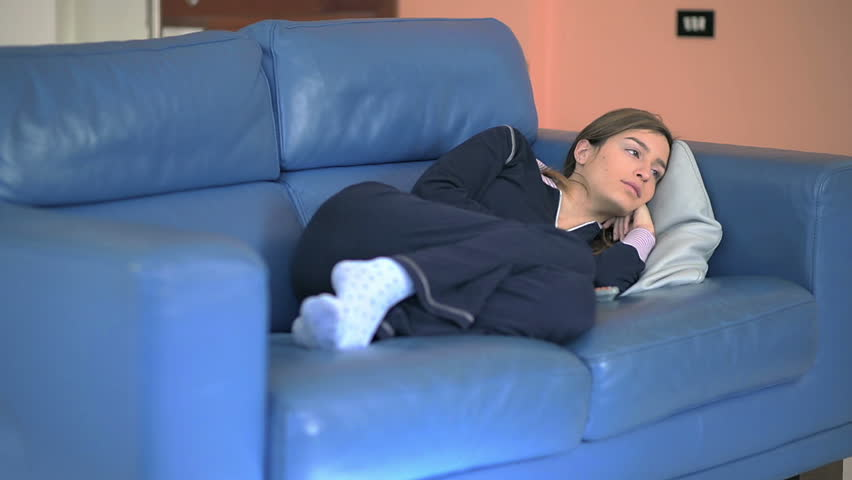 06e64aae05 Young woman watching TV sitting on the couch at home. S. By SEEDREAM. Stock  footage ID  5750045. Video clip ...