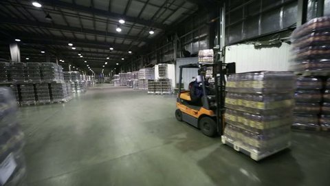 Lot of packaged beer bottles in large warehouse and loader machine.