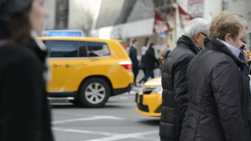 NEW YORK CITY - FEBRUARY 23 2014. Crowds of people crossing the street along Fifth Avenue in Manhattan as Shoppers and Business people brave the cold weather of winter in New York. NEW YORK.