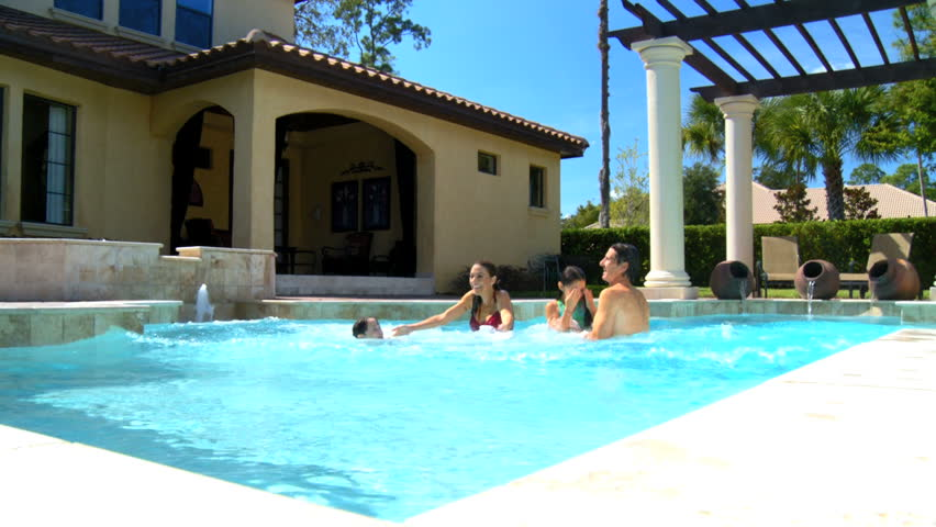 Attractive young caucasian family enjoying  leisure time together in their luxury swimming pool 60 FPS