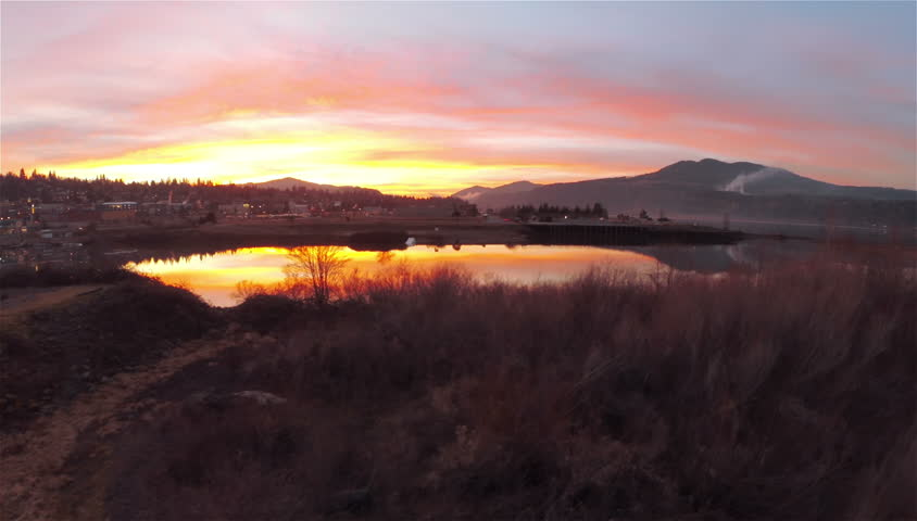 2.7K Ultra HD Very Smooth Aerial Shot Rising Up Over Small Water Port Town During an Amazing Colorful Sunset with Rolling Hills in the Background with Smoke HD Video