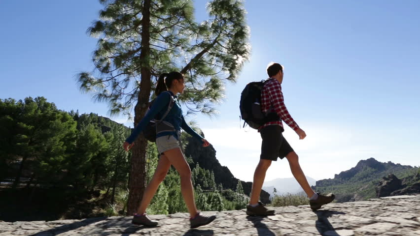 Hikers couple walking on trail. Hiking people walking in mountains. Young woman and man hikers on path to Roque Nublo, Gran Canaria, Canary Islands, Spain.