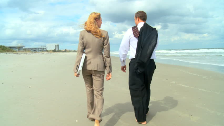 Two young business people escaping the office to walk on the beach 60 FPS
