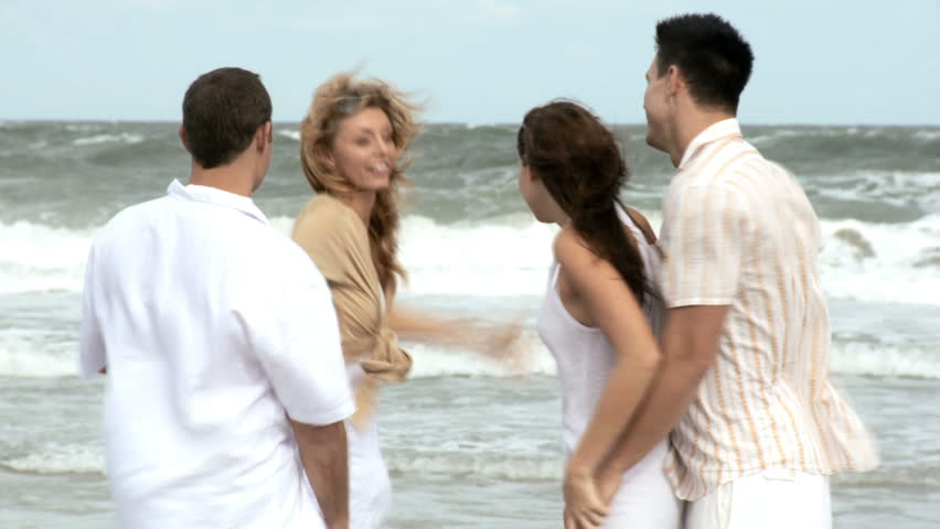 Four attractive young adult friends having crazy fun on the beach together 60 FPS