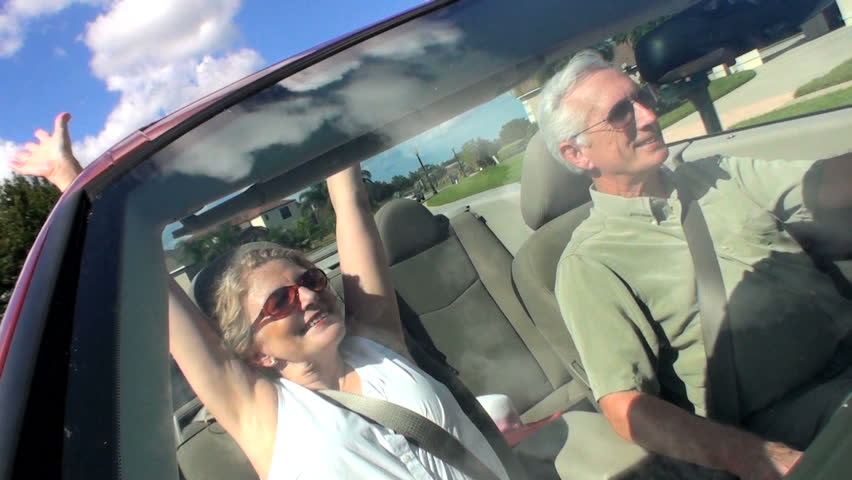 Contented retired couple enjoying driving home in the sunshine in their open top car