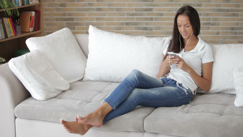 Hy Wearing Earphones Relaxing On Sofa Using Mobile Phone Looking At Camera And Smiling