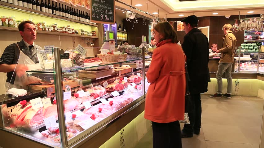 PARIS, FRANCE - OCTOBER 16 : parisian customers buying meat in the butcher's shop of the rue Montorgueil on October 16th, 2013 in Paris, France