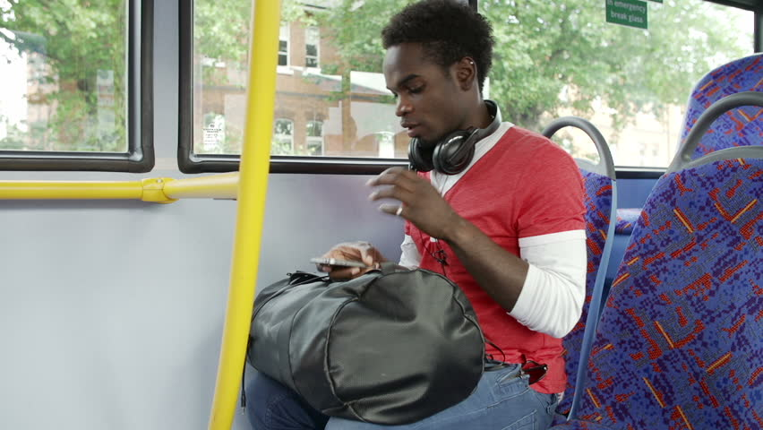 Young man using mobile phone on bus,rushes to get off at stop but leaves phone on seat as camera zooms in.Shot on Sony FS700 in PAL format at a frame rate of 25fps