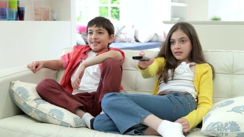 Children sitting on sofa fighting over tv remote control.Shot on Canon 5d Mk2 with a frame rate of 25fps