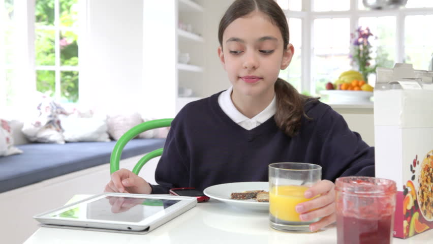 Schoolgirl sitting at kitchen counter drinking juice whilst using tablet computer and mobile phone.Shot on Canon 5d Mk2 with a frame rate of 25fps
