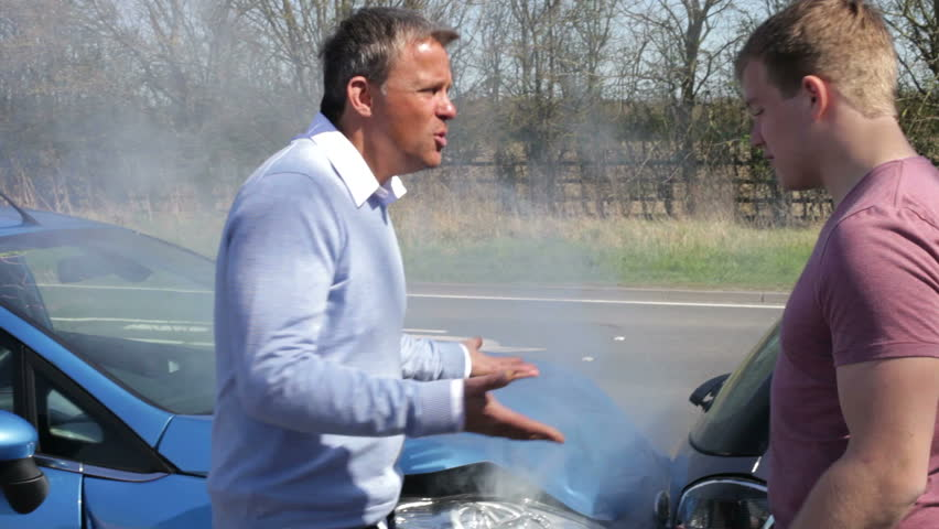 Two drivers argue about blame for accident by the side of damaged and smoking vehicles.Shot on Canon 5d Mk2 with a frame rate of 30fps