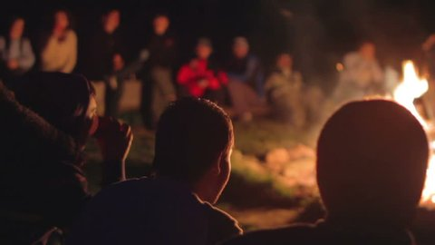 young people gathered around campfire at camp
