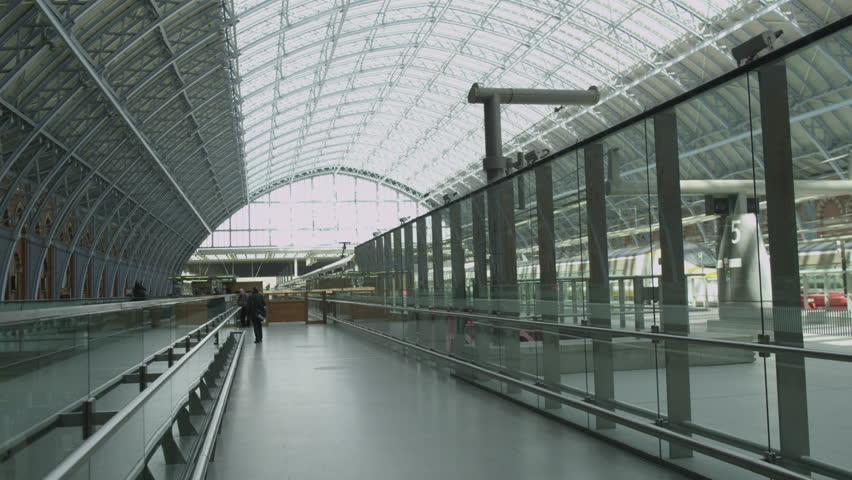 Interior view of St. Pancras railway station, London featuring the glass ceiling and clock on the wall. #5897045
