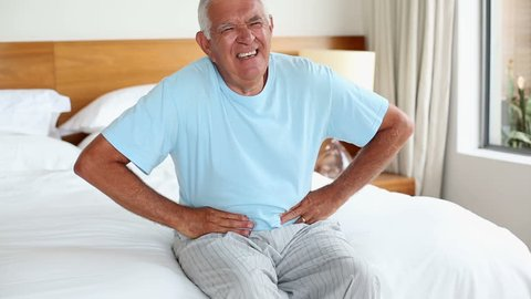 Senior man sitting on bed with a stomach ache at home in the bedroom
