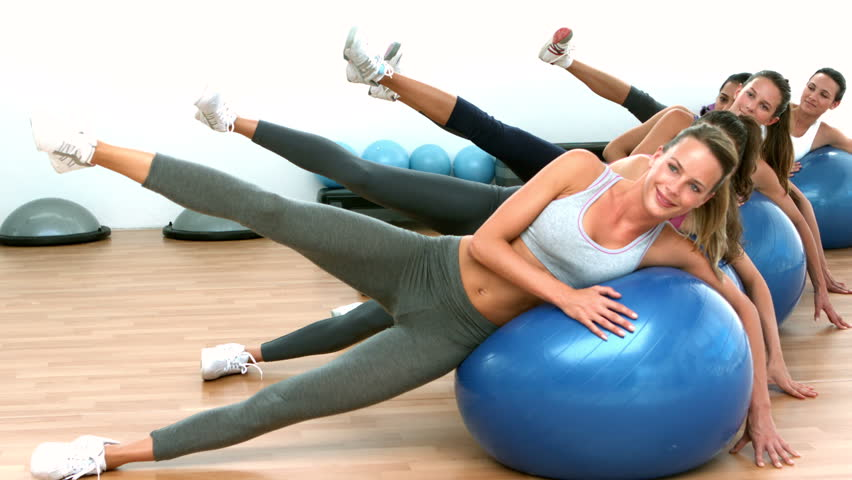 Fitness class exercising on on exercise balls in slow motion