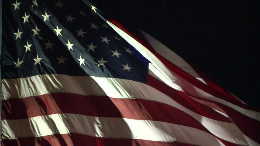 AMERICAN FLAG USA WAVING LITE AT NIGHT IN WIND LONG 30 SECOND SLOW MOTION CLIP