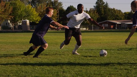 High school boys playing soccer in the park - 4K