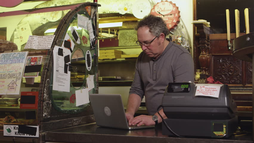 Small business owner working at cash register - 4K