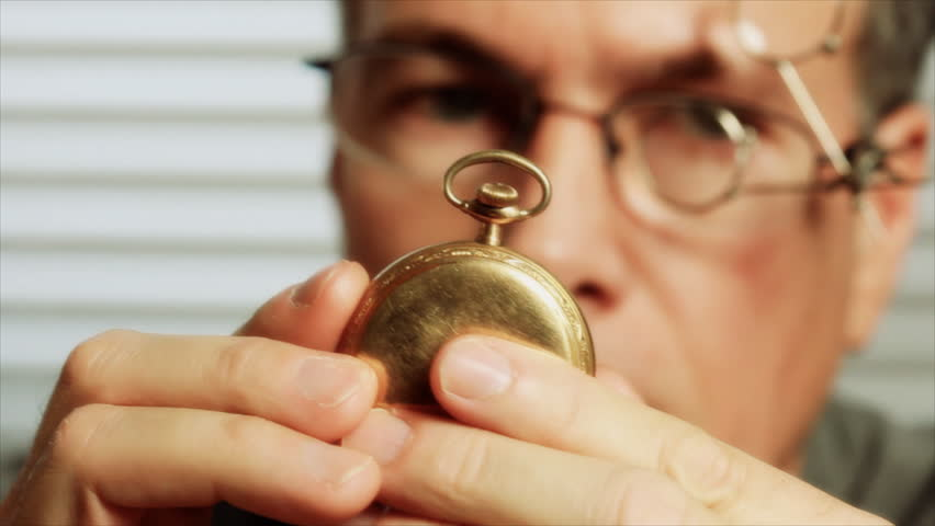 A man wearing jewelers glasses, picks up an old pocket watch and begins to examine it. Rack focus
