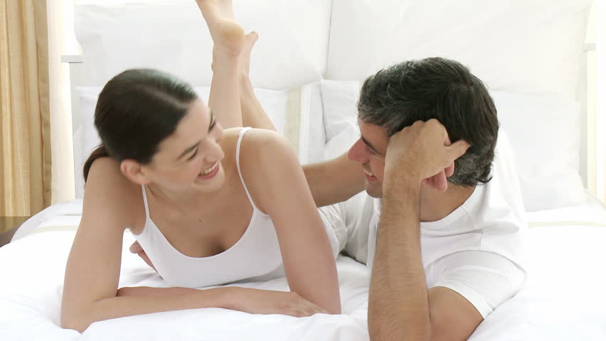 Happy young couple talking on bed. Concept of love and happiness. Footage in high definition