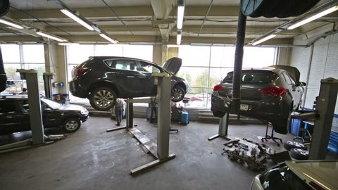 Cars on lifts and on floor at car workshop for repairing