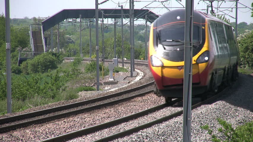 Northamptonshire, UK - May 2008: A Virgin Trains Pendolino tilting passenger train rounds a bend at high speed on the West Coast railway mainline. Railway franchise and transport.