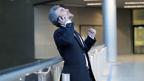 successful business man talking at smart phone  celebrate a good news at dusk