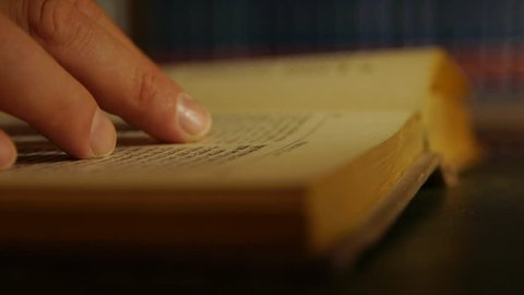 Hand / finger over law book while reading. Turning pages. Close up, night / dusk. Law, bible, university text / novel.
