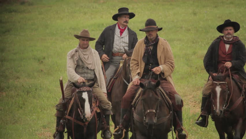 VIRGINIA - 2013.  Western era, Old West Cowboy, Marshall, Sheriff, Outlaw on horseback.  Circa 1860-1890s.  Men on horseback, galloping, riding, trot in pairs and in a group. riding in open west field