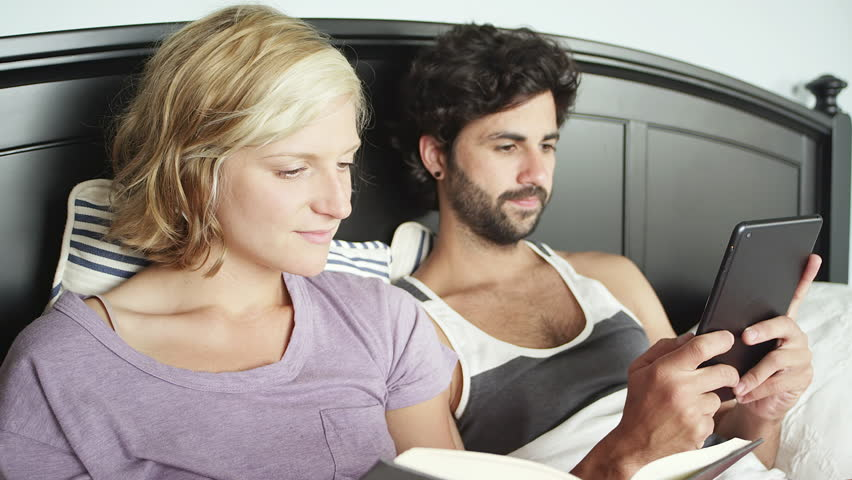 Close up shot of a young couple laying in bed while the woman reads a book and the man looks through his tablet