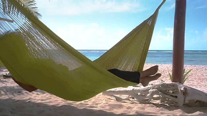 Sleeping in hammock on caribbean beach at Mahahual, Quintana roo, Mexico