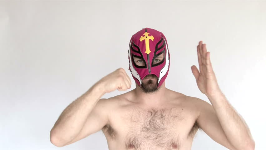 Model released man in studio wearing red lucha libre mask wrestles and challenges viewer.