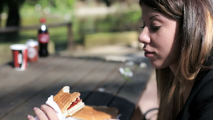 Beautiful young woman eating a hot dog in a park   Shutterstock HD Video #6091190