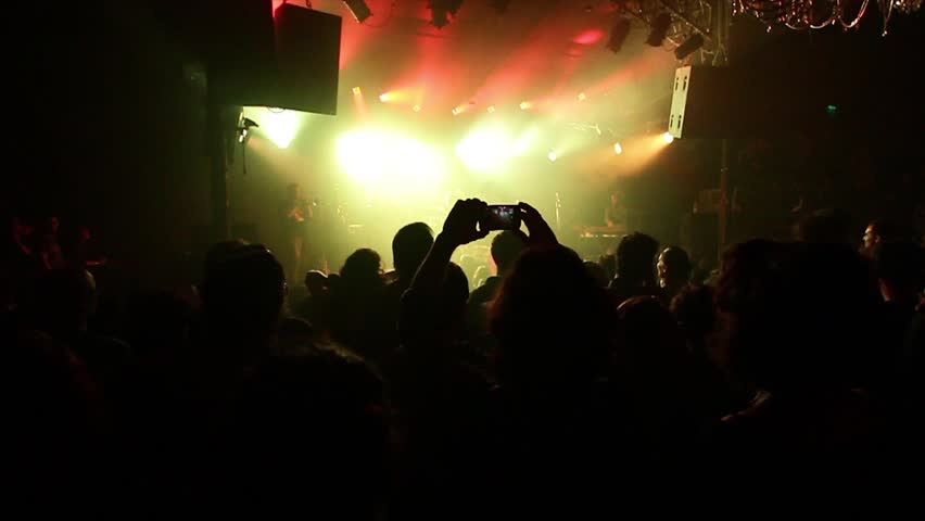 A person recording video with his phone in Club Show with crazy lights- slow motion