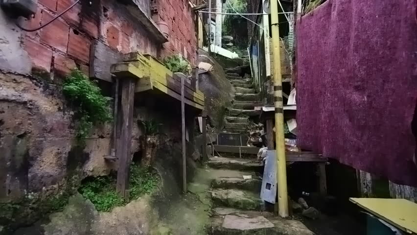 Tracking shot of crowded shanties along the stairs in a favela in Rio de