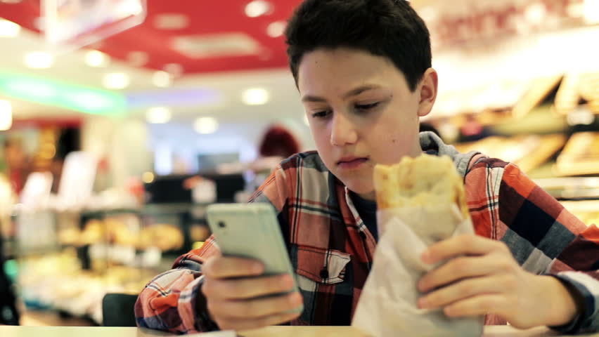 Teenager texting on smartphone and eating sandwich in cafe