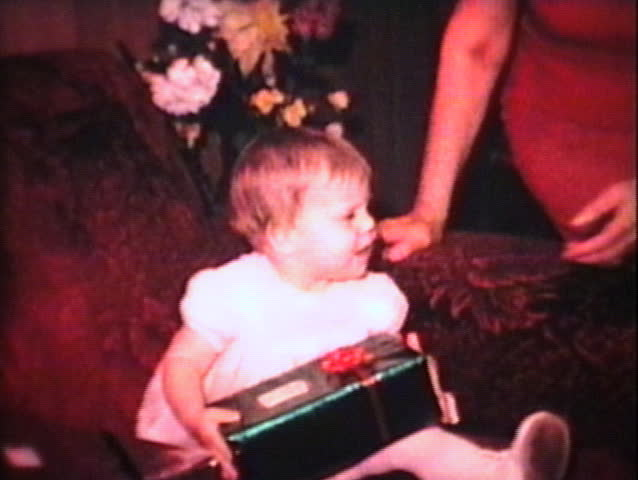 A cute little baby girl is very excited to receive her first Christmas present from her mother. (Vintage 8mm film)