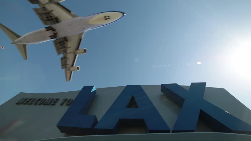 LOS ANGELES - CIRCA 2014: Jet planes approaching on final approach before landing at LAX, Los Angeles International Airport fly past the welcome to LAX sign