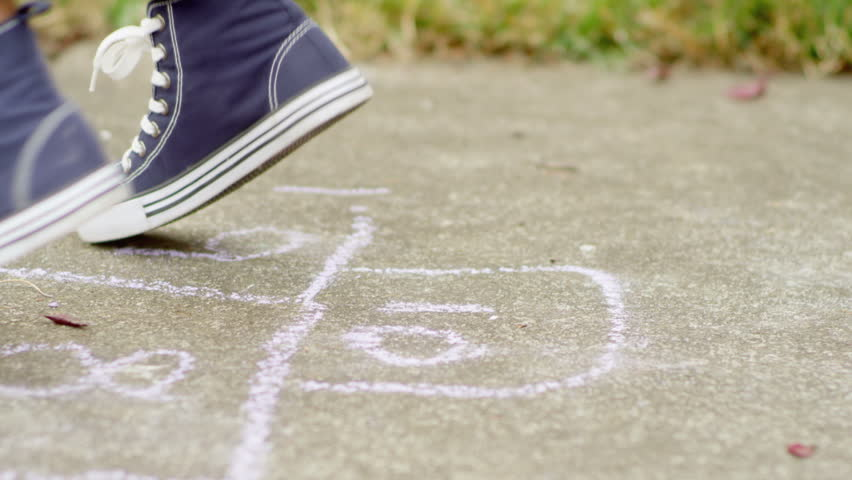 Slow motion tracking shot of a pair of feet jumping while playing hopscotch