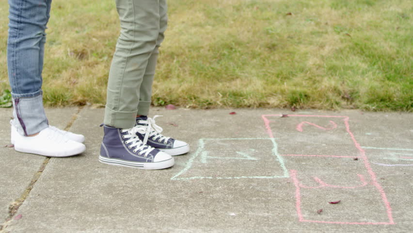 Close up tracking shot of a girl jumping while playing hopscotch