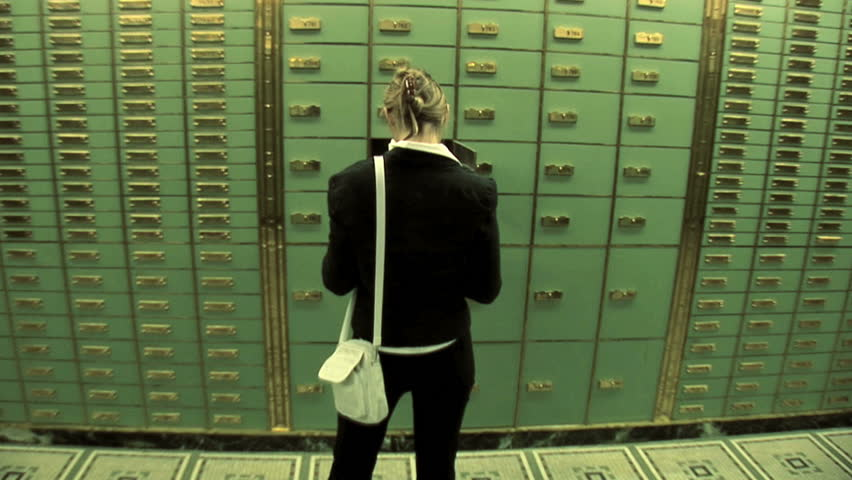women standing in front of locker. save savings. top secret. withdraw. money cash. security. safety safe. investment. banking