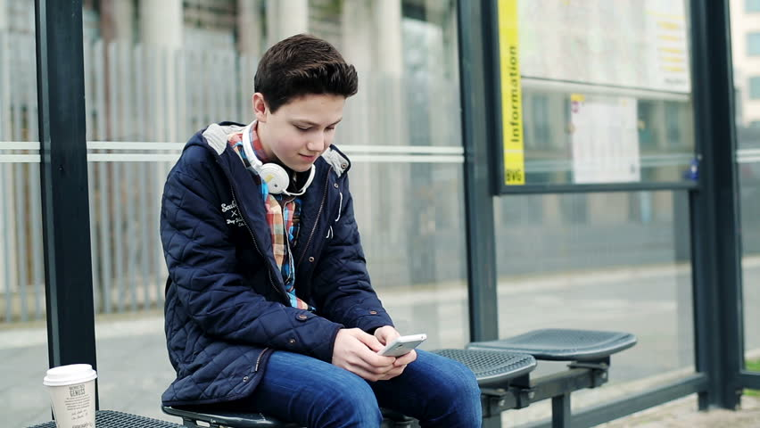 young boy with headphones listen to the music sitting on