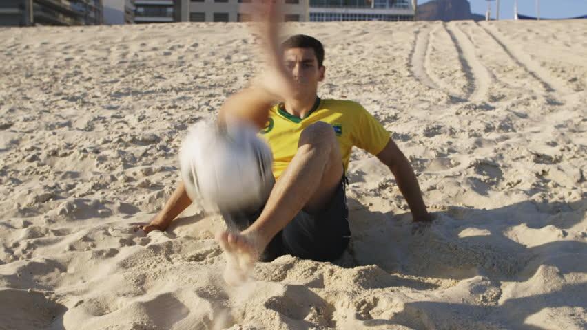 MS A man practices tricks with a football on Ipanema Beach / Rio de Janeiro, Brazil