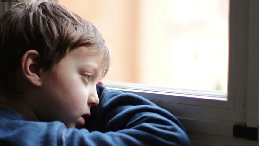 child sad and lonely looking through window