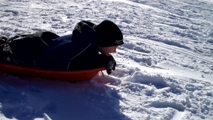boy tobogganing head first down a snowy hill