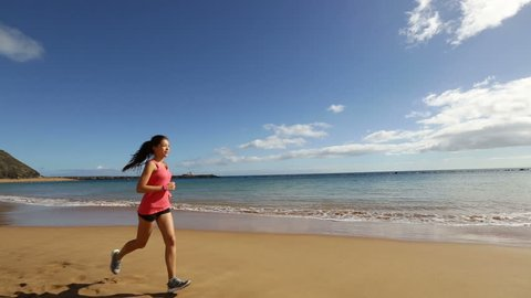 Jogging woman jogging using heart rate monitor stopwatch while jogging on beach. Sport fitness girl exercising and training outside under blue sky by the sea. Mixed race Asian Caucasian model.