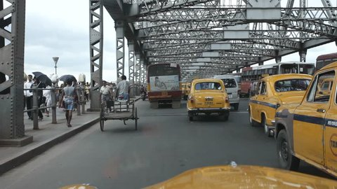 KOLKATA (Calcutta), INDIA - SEPT.2011:  Yellow Ambassador taxi cabs goes on the Howrah bridge on September 21, 2011. Hindustan Ambassador is a car manufactured by Hindustan Motors of India since 1958.